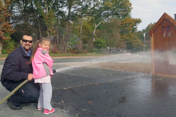 Avery DaCosta of Bellingham, age 5, and her father, Lt. DaCosta spraying the fire house.