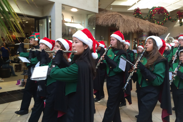 The clarinet section of the Mira Costa Marching Band marches through the mall