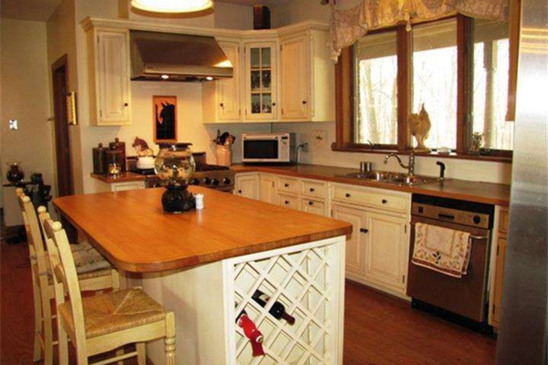 The kitchen features a Viking stove, work island and wine bar.