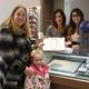 Colleen Condon is presented with her prize, a beautiful pearl necklace, by the staff of Bernard Jewelers.