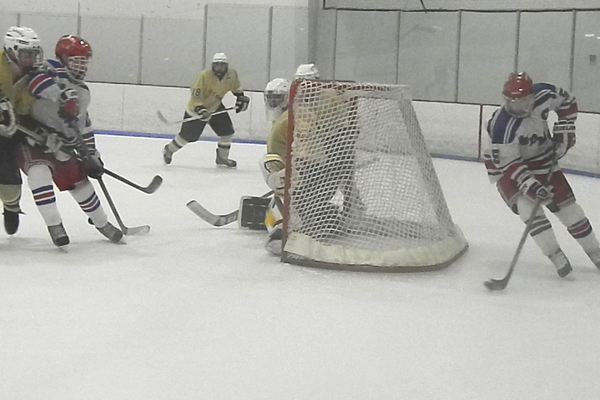 Tewksbury's Ryan Meade (5) circles the goal looking for David Dempsey (12) who is crashing the net.
