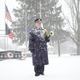 """A snow-covered bugler stands at attention after sounding """"Taps"""" for Richard Pinter, who was known as The Lone Bugler."""