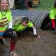 Stacey Finnegan, Karla Branchaud, and Linda Poli wiggle their way through a tunnel partly submerged in mud.