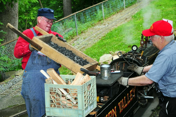 Volunteers firing up a steam locomotive in preparation for a Steamin' Day event. Firing up takes about one hour for this 1/8-size locomotive. Credit Mike Ciosek