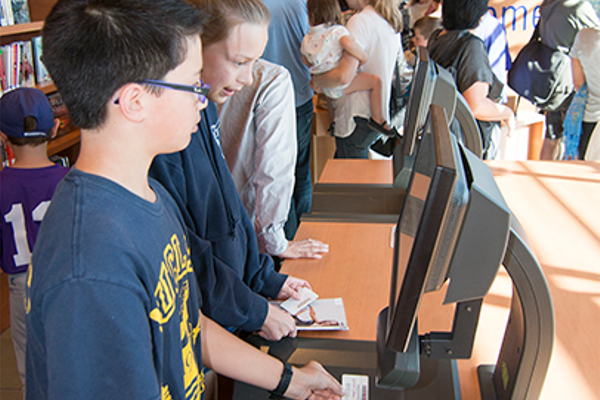 Eager youths were among the first to use the new self-checkout system. Photo by Brad Jacobson.