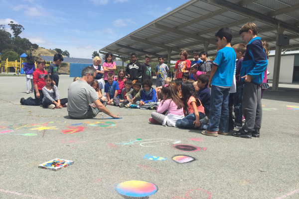 Chalk artist Mark Wagner talks about the playground art project to Valhalla students.