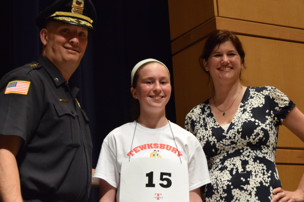 Wynn School's Meghan Ostertag won the TEF 7th Grade Spelling Bee. She is flanked by Deputy Police Chief John Voto and Children's Librarian Noelle Boc.