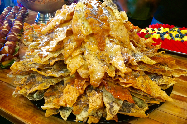 A stack of Lithuanian crispy crepes with honey, sugar, raisins, and poppyseeds