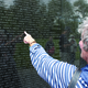 An unidentified woman points to the name of a loved one at the Vietnam Wall. Photo by Bud Elliott.