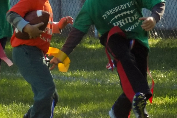 Green pride defender Jack Leone reaches for a tackle against Orange Pride's Max Curley in a Tewksbury Flag Football showdown. Courtesy photo.