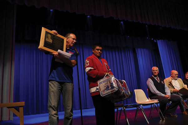 (Left to right) Ben Lomond High principal Dale Wilkinson holds a Wall of Fame plaque and student Jesus Oseguera stands by with gifts for honorees Kerry Favero and Mikel Vause.