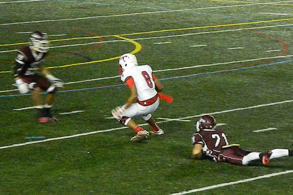 Senior wide receiver Adam Gajjaoui (8) eludes two Chelmsford defenders.