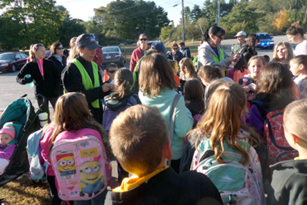 "Safe Routes to school coordinator Suzanne Walton hands out ""I walked to school"" stickers to children who participated in the fall event."