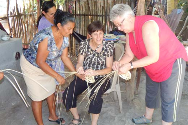 Skill-learning is a two-way street. Here the American volunteers are learning basket weaving from the Honduran women