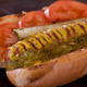"""The SuperFan"" All-beef hot dog, Chicago style on a plain bun with yellow mustard, sweet relish, fresh tomato, kosher dill spear, sport peppers and celery salt."