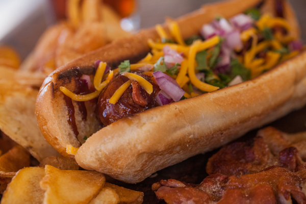"Most popular ""The Danger Dog"" Bacon-wrapped, deep fried spicy hot link on a plain bun with tangy barbecue sauce, Sriracha chili sauce, and cheddar cheese topped with fresh cilantro and red onion."