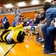 Bumble of the Salt Lake Bees plays with a dog to the delight of the audience at the Mascot Miracle Foundation Pep Rally. – Camera Shy
