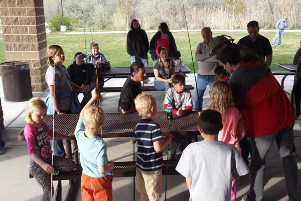 Instructors teach kids how to tie fishing knots during the youth fishing program. —Josh Allred