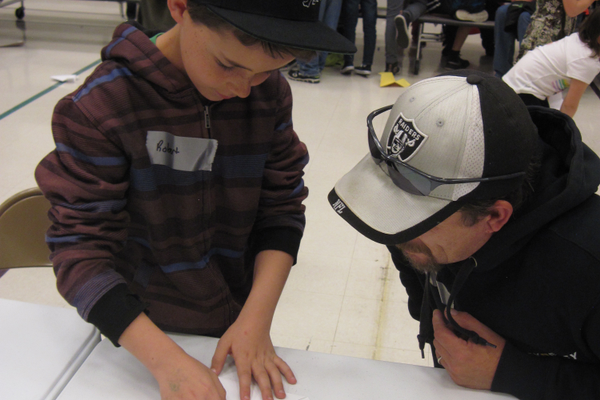 A dad and son construct a paper airplane at the Dad and Kid Science Night at Columbia Elementary School. – Stacey Leavitt