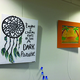 """Alexus Powell's dreamcatcher artwork and Kameryn Grose and Livia Anderson's """"Hawaiian Sunset"""" hang on one of the upstairs walls in the Old Dome Meeting Hall. – Tori La Rue"""