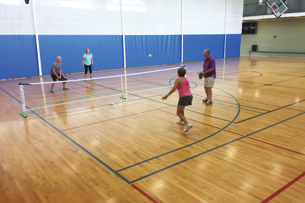 Four members of the Holladay Lions Recreation Center play a quick match of pickleball on a Friday morning. The first team to score 11 points by a two-point margin wins. —Sarah Almond