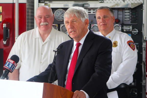 Foreground: ParentsEmpowered representative Mike Brown asking parents to reconsider allowing of faciliting underaged drinking. Background: Sandy City Mayor Tome Dolan and Sandy City Fire Chief Bruce Cline at the press event announcing the release of ParentsEmpowered videos featuring Sandy firefighters and the display of anti-underaged drinking graphics on various Sandy firefighting vehicles at Sandy City Fire Station 31 on June 30, 2016. (Photo: Chris Larson, Sandy City Journal)