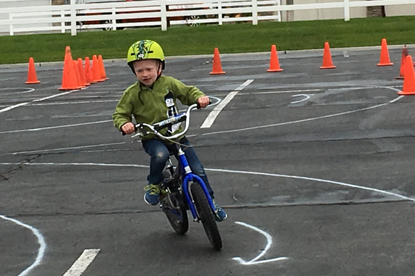 A child rides through the bicycle rodeo obstacle course at Heathy Herriman's Pedal Palooza. The goal of the event is to teach children about bicycle safety. – Tori La Rue