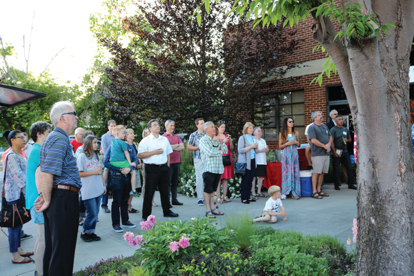 Sugar House residents listen to remarks made by city councilmember Lisa Adams at the lighting ceremony in front of the United Natural Products Alliance historic building.