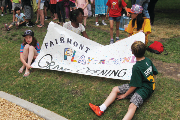 Kids hold the sign for the Fairmont Park playground grand opening shortly before the ceremony begins. —Travis Barton