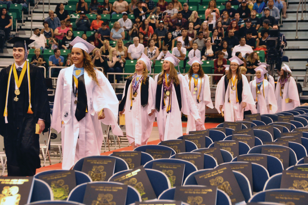 Students walk through their processional excited for the postgraduate feelings to begin. —Island Photography