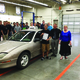 Alek Arpero stands next to Principal Craig Stauffer and Debbe Jones in Arpero's shop class after being given the keys and car title to a '97 Pontiac Sunfire. —Eric Bailey