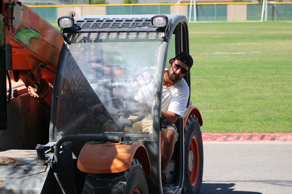 A FieldTurf employee loads a several hundred pound bag of washed silica sand onto a fork lift for fill in the new Jordan High School turf field. (Photo: Chris Larson, Sandy City Journal)