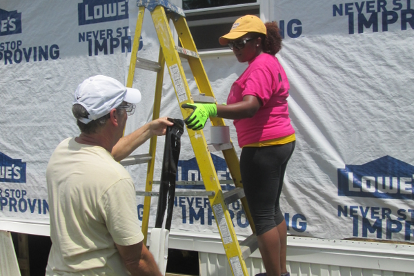 A teen worker installs a new window with the help of an adult at the job site.