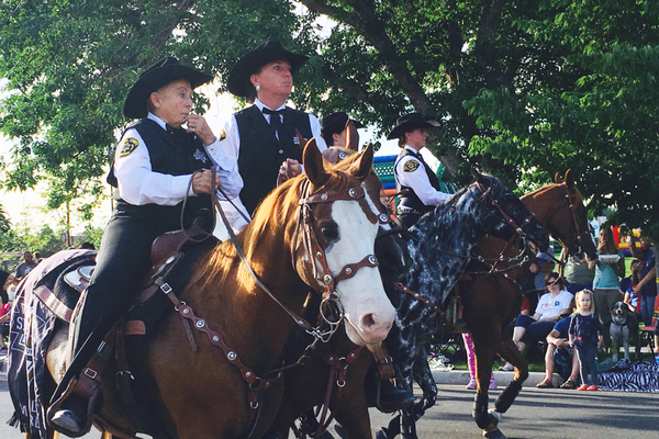 Representatives from the Salt Lake County Sheriff's office ride horses through the Riverton City Town Days parade route. –Tori La Rue