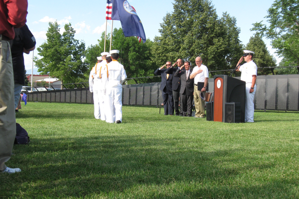 Mayor Ron Bigelow places his hand over his heart as Congressman Chris Stewart and Colonel Gary Harter salute the flags during the opening ceremony of The Wall That Heals at Centennial Park. As part of its tour, the wall is a half-scale replica of the Vietnam Veterans Memorial in Washington DC. –Travis Barton