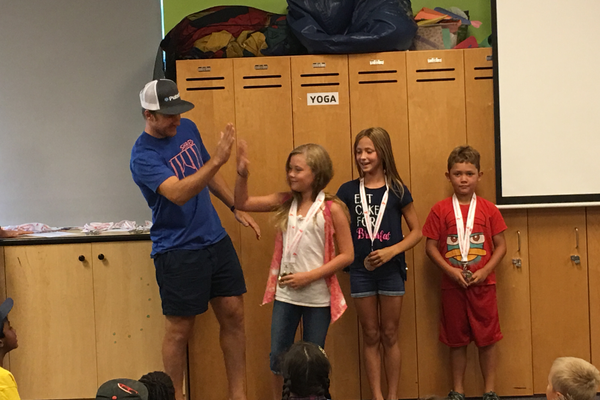 Ted Ligety, two-time Olympic gold medalist, gives Anabelle Latta, 9, a high-five after presenting her with a gold medal for her second season of Alpine skiing through the Ted Ligety Learn to Ski Program. –Tori La Rue