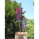 A member of Team Valor from the Pokémon Go game stands on top of a park monument with his team's banner at Murray Park. –Travis Barton
