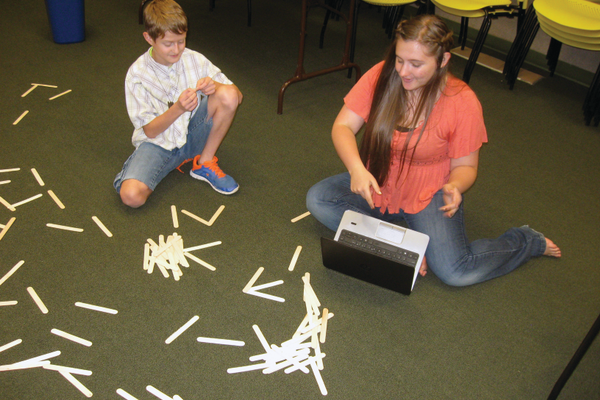 Utah State University student Melissa Ivie explains some engineering techniques to Corbin Carpenter during the Junk Drawer Robotics Camp at West Valley Library on Aug. 8. –Travis Barton