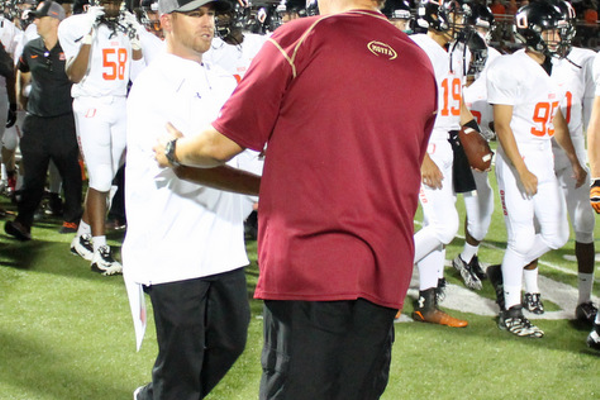Maple Grove Head Coach Matt Lombardi and Osseo Head Coach Ryan Stockhaus shake hands following the Crimson 23-13 win.