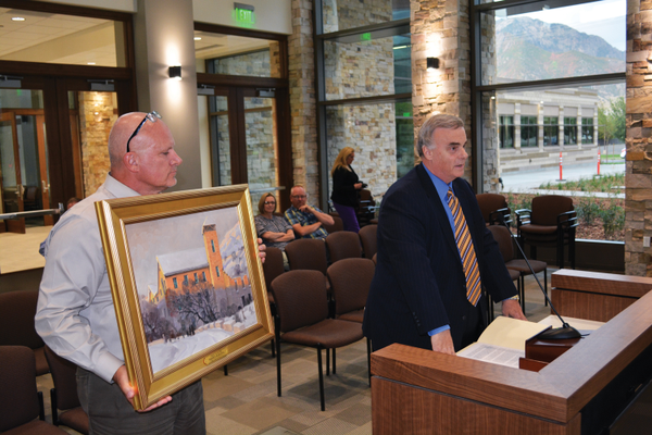 Community and Economic Development Director Brian Berndt holding a housewarming gift given by City Attorney Shane Topham. (Dan Metcalf Jr./Cottonwood Heights)