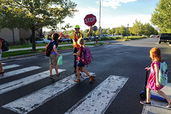 Daybreak Elementary crossing guard Don Hicks has been known to give high-fives and a joke to students to start their day off with a smile. (Julie Slama/My City Journals)