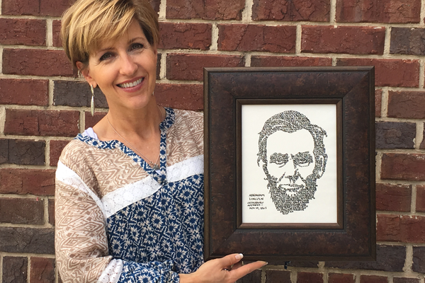 Lori Howell holds a piece of artwork she created using calligraphy of the Gettysburg Address to form the image of Abraham Lincoln's Face. (Tori La Rue/City Journals)