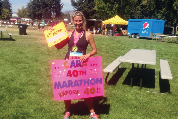 Cara Hasebi holds up signs her friends and family made for her after completing her 40th marathon before turning 40 years old. (Cara Hasebi/Resident)