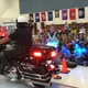 Officer Andrew Hercules of the West Jordan Police Department rides a motorcycle into the Heartland Elementary School safety assembly. (Tori La Rue/City Journals)