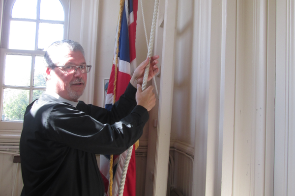 Rector John Schaeffer rings the church bell.