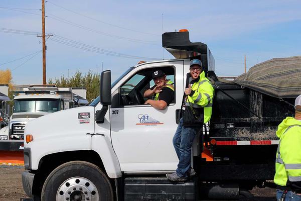 Mitchell Ackley and Eric Trigg, two of the new operations specialists for the Cottonwood Heights Public Works team, show off one of the new trucks that will be used for the upcoming winter season. (Cassie Goff/City Journals)