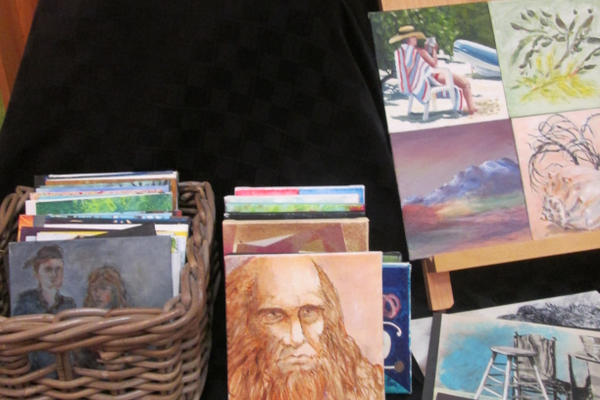 A bin full of small paintings by local artists, for sale at $30, with all proceeds benefitting a scholarship fund.