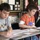 Charlie Maraganis and Garrett Ayotte writing their notes.