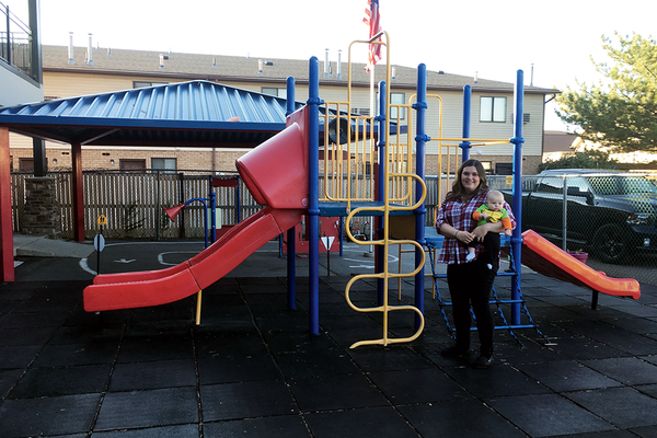 Cournie Angeli, nature explore program specialist, stands in front of the playground with her son. Angeli coordinated the outdoor classroom design earning ABC Beginnings-Redwood a national recognition. (Travis Barton/City Journals)