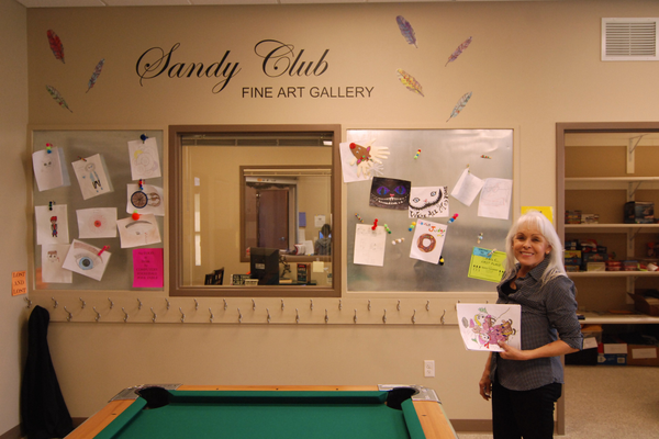 : Linda Martinez Saville in front of the Sandy Club Art Gallery wall. (Keyra Kristoffersen/City Journals)